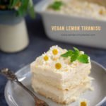 A slice of vegan lemon tiramisù on a plate with some flowers in the background.