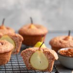 Wholesome vegan pear muffins on a tray. One muffin is sliced in half to reveal the pear.